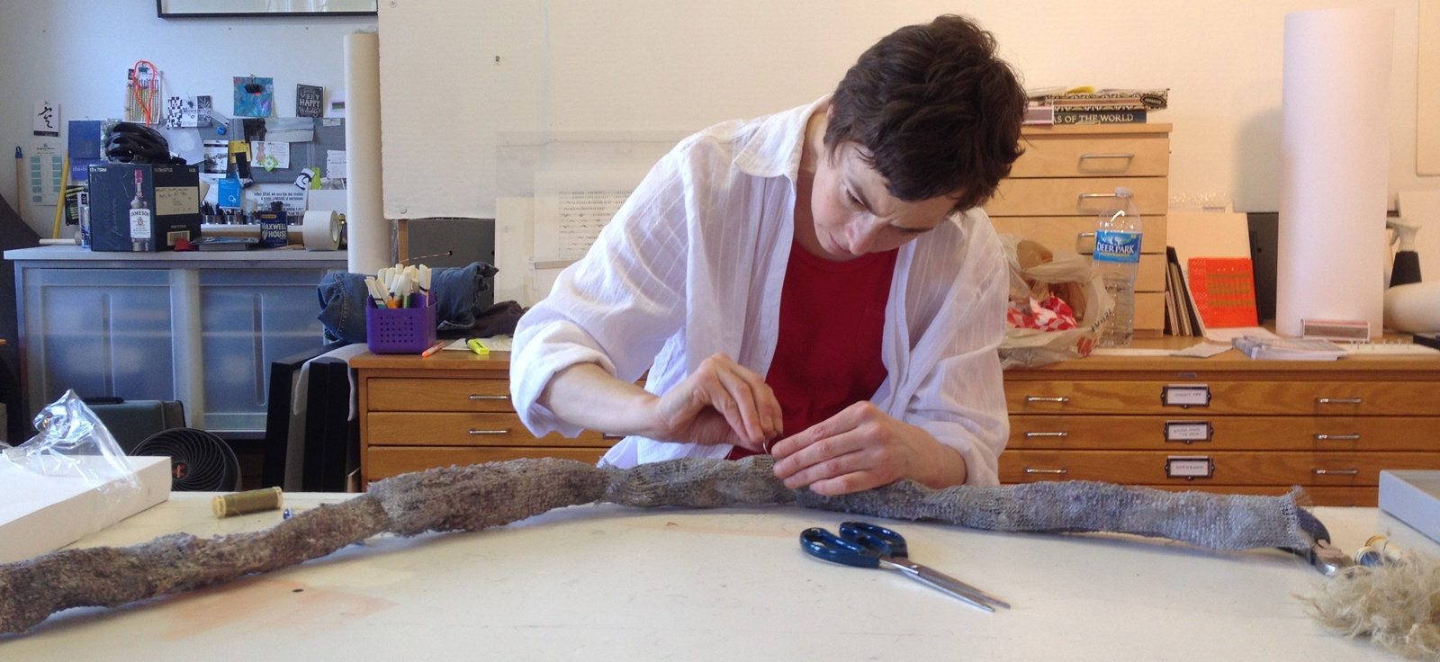 Amy Ralston working on a new piece using found fiber.